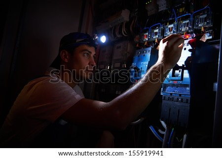 electrician worker detecting and fixing wire cabling damage breakdown with tester scredriver in power distribution fuseboard - stock photo