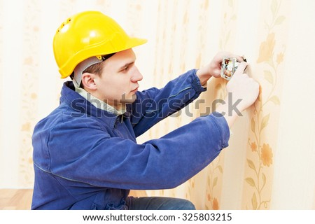 electrician worker installing and light switch or power wall outlet socket - stock photo