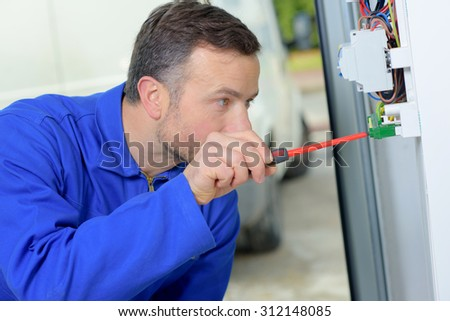 Electrician working on a fusebox - stock photo