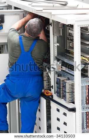 electrician working on an industrial power distribution center - stock photo
