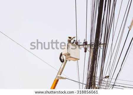 Electrician working repairing the power line on hydraulic platform - stock photo