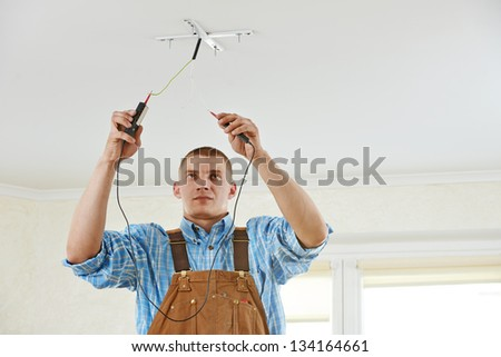 electrician working with cable checking phase of current during wiring work - stock photo