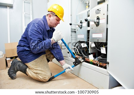 electrician working with cable wiring crimping tool at distribution electric power box - stock photo