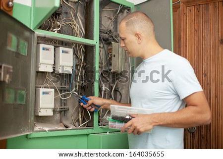 electrician working with electric box at house - stock photo