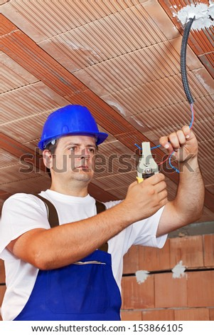 Electrician working with the ceiling wiring in a new building - stock photo