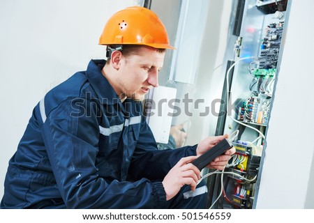 Electrician works with electronic equipment