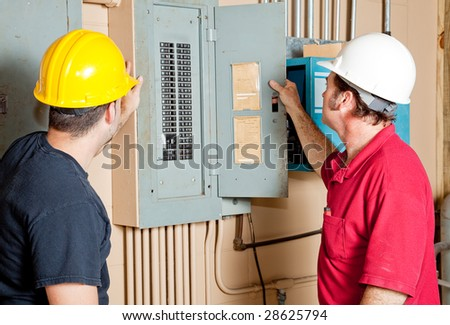 Electricians examining a circuit breaker panel in an industrial setting. - stock photo