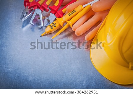 Electricians gloves building helmet electrical tester pliers nippers insulation strippers on metallic background. - stock photo