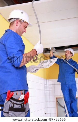 Electricians installing electrical cabling - stock photo