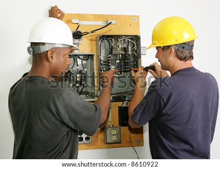 Electricians repairing breaker panel.  Actual electricians performing work according to industry safety and code standards.
