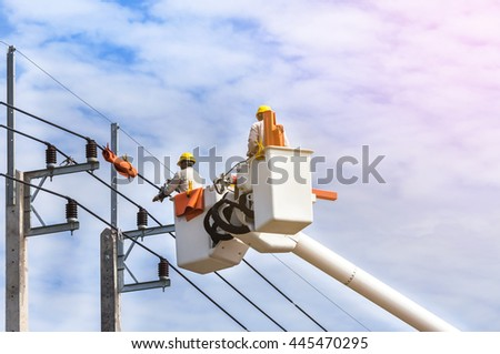 electricians repairing wire of the power line on electric power pole  - stock photo