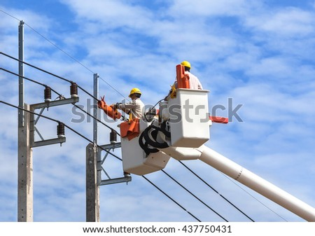 electricians repairing wire of the power line on electric power pole with hydraulic platform  - stock photo