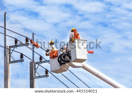 Electricians repairing wire of the power line with basket hydraulic lifting platform vehicle   - stock photo