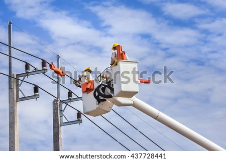 electricians repairing wire on electric power pole with hydraulic platform.