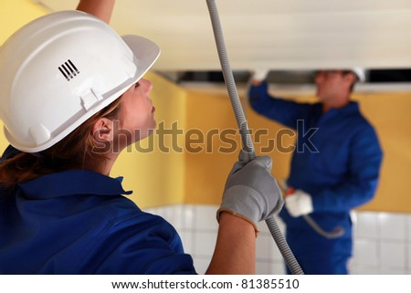 Electricians wiring a large room