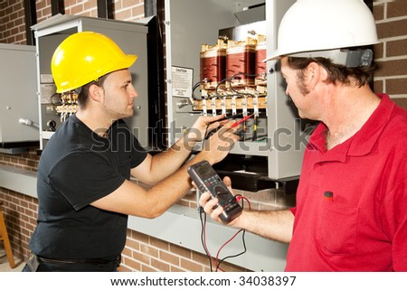 Electricians working on an industrial power distribution center.  Actual electricians and authentic accurate content. - stock photo