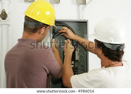 Electricians working together to install a breaker panel.  Models are actual electricians - all work is performed according to industry standard code and safety practices. - stock photo