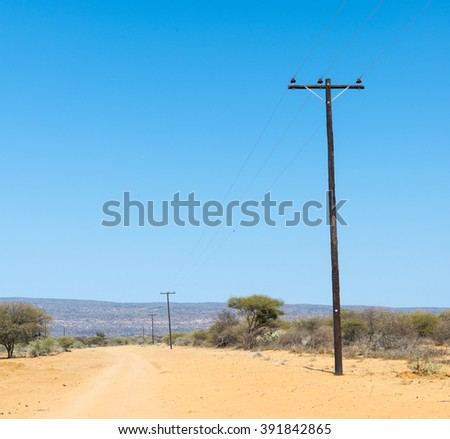 Electricitiy power lines running along a dirt road in Botswana, Africa - stock photo