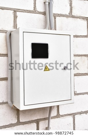 Electricity control box on house wall - stock photo