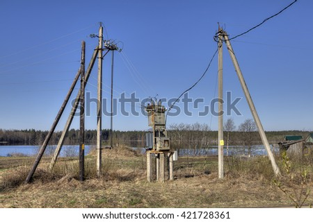 Electricity distribution transformer, electrical power substation in the countryside spring sunny morning.