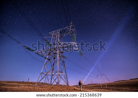 Electricity power poles on alone man -  night sky and stars background - stock photo