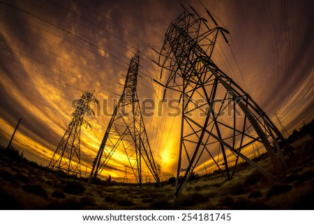 Electricity power pylons at sunset - stock photo