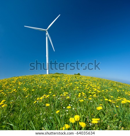 Electricity power wind turbine against blue sky background - stock photo