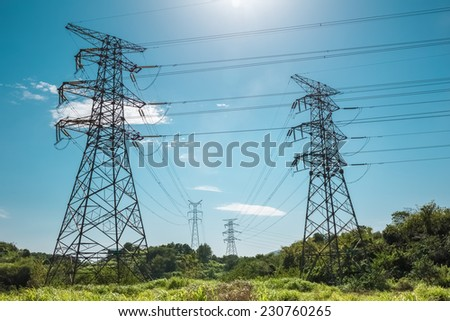 electricity pylon against a blue sky , power transmission background  - stock photo