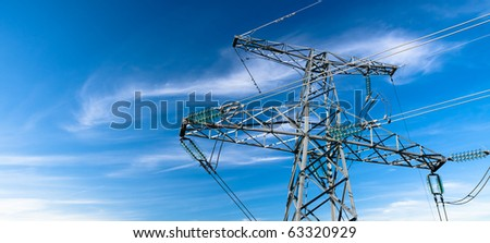 Electricity pylon against blue cloudy sky - stock photo