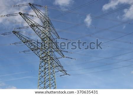 electricity pylon against blue sky - stock photo