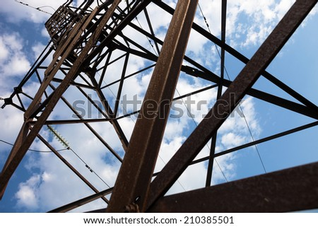 Electricity pylon against the cloudy sky background. - stock photo