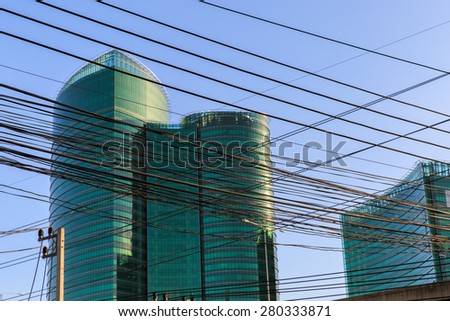 Electricity pylon and power-line on building background in bangkok city - stock photo