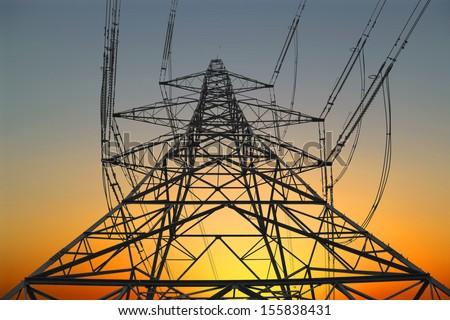 electricity pylon at sunset - stock photo