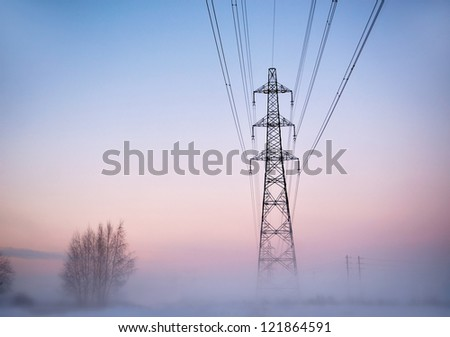 Electricity pylon in heavy fog at sunset in winter - stock photo