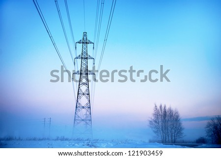 Electricity pylon in heavy fog at sunset in winter