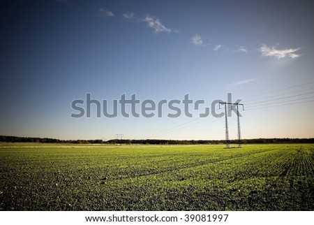 Electricity pylon on a green field in sunset