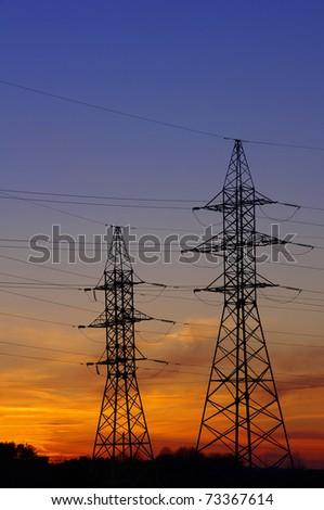 Electricity Pylon over orange sunset sky - stock photo