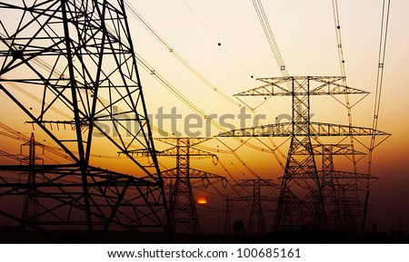 Electricity Pylon over orange sunset sky, environmental damage