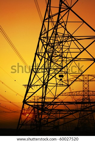 Electricity Pylon over orange sunset sky. Environmental damage - stock photo