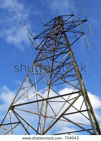 Electricity pylon/tower against white fluffy cloud blue sky