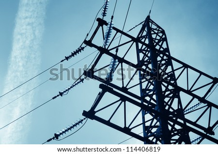 Electricity pylon with insulators and power lines. Blue sky background. Blue color toned