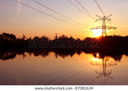 Electricity pylon with reflection in water at sunset - stock photo