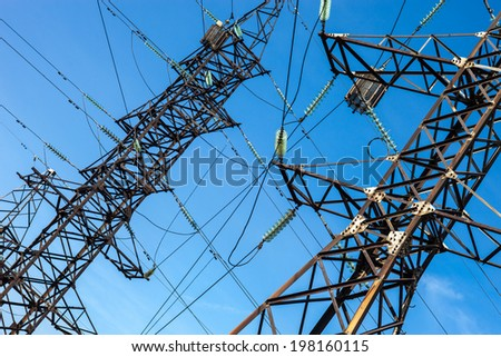 Electricity pylons against the blue sky background.
