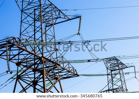 Electricity pylons against the blue sky background. - stock photo