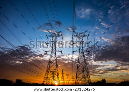 Electricity pylons and cable lines during sunset. Horizontal format - stock photo