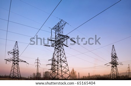 Electricity pylons and lines at dusk. - stock photo
