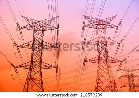 Electricity pylons and lines at sunset  - stock photo