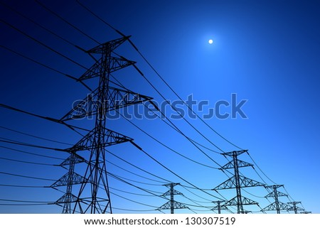 Electricity pylons and lines on a clear blue sky. - stock photo