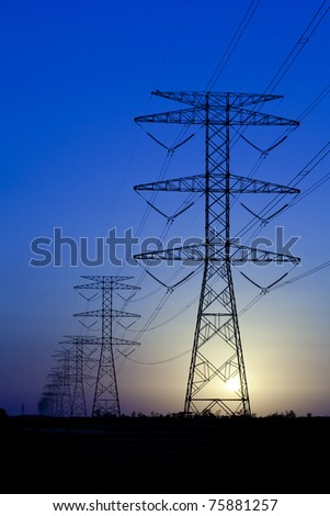 Electricity pylons and sun against blue sky - stock photo