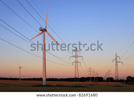 Electricity pylons and wind turbines against sky at sunset - stock photo